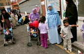 Young women and their families enjoy a fairground at the opening of The London Muslim Centre, East London. - Jess Hurd - 12-06-2004