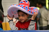 Young boy with a Union Jack hat at a fairground. Opening of The London Muslim Centre, East London. - Jess Hurd - 12-06-2004