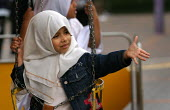 Young girl on a fairground ride at the Opening The London Muslim Centre, East London. - Jess Hurd - 12-06-2004
