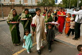 The bridegroom arrives with his family to the traditional Mehndi Wedding Ceremony. Tower Hamlets, East London. - Jess Hurd - 29-07-2004