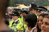 Police watching, thousands of people at the London Mela, the largest South Asian gathering in Europe. West London. - Jess Hurd - ,2000s,2004,adult,adults,Asian,BAME,BAMEs,Black,BME,bmes,camera,cameras,carnival,Carnivals,CELEBRATE,CELEBRATING,celebration,CELEBRATIONS,clj crime,communities,community,cultural,dance,DANCER,DANCERS,
