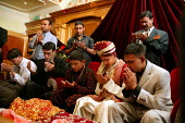 The bridegroom and male family members say prayers at a traditional arranged Wedding and Walima ceremony. Suleymanie Mosque. Dalston, East London. - Jess Hurd - 01-08-2004