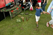 Small child walks past a land mine display part of the British Army recruitment stall at the London Mela, the largest South Asian gathering in Europe. West London. - Jess Hurd - 15-08-2004