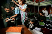Children try to do their homework in a cramped bedroom. Bengali family, Sanur Ali with wife Salima Begum and their five children living with two other relatives in a damp and crowded two bedroom counc... - Jess Hurd - 02-10-2004