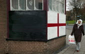 A young asian woman walks past St Georges Flag with Racists scrawled on it outside an East London Pub. - Jess Hurd - 2000s,2005,asian,asians,BAME,BAMEs,bangladeshi,Bangladeshis,bengali,bigotry,black,bme,BME black minority ethnic,bmes,bought,buy,buyer,buyers,buying,cities,city,commodities,commodity,consumer,consumers
