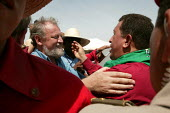 President Hugo Chavez of Venezuela (right) embrasses Joao Pedro Stedille MST leader on a visit to a Movimento dos Trabalhadores Rurais Sem Terra (MST, Landless Workers Movement) occupation in Tapes. W... - Jess Hurd - 30-01-2005