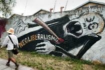 World Social Forum, Porto Alegre Brazil. Delegate walks past anti Neoliberalism graffiti. - Jess Hurd - 25-01-2005