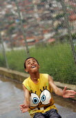 Teenager playing in Magdalena Favela, Sao Paulo where families live in slum housing, Brazil. - Jess Hurd - 03-02-2005