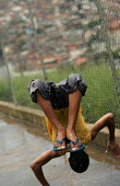 Teenager playing in the rain, Magdalena Favela, Sao Paulo where families live in slum housing, Brazil. - Jess Hurd - 03-02-2005