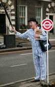 Commuters queue at a mock bus stop on Bedford Square London W1, dressed in pyjamas and slippers to promote the TUC Work Your Proper Hours Day. London. - Jess Hurd - 2000s,2005,activist,activists,adult,adults,asleep,bowler hat,bus,bus service,bus stop,BUSES,CAMPAIGN,campaigner,campaigners,CAMPAIGNING,CAMPAIGNS,COMMUTE,commuter,commuter commuters,commuters,commutin