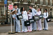 Commuters queue at a mock bus stop on Bedford Square London W1, dressed in pyjamas and slippers to promote the TUC Work Your Proper Hours Day. London. - Jess Hurd - ,2000s,2005,activist,activists,adult,adults,asleep,bowler hat,bus,bus service,bus stop,BUSES,CAMPAIGN,campaigner,campaigners,CAMPAIGNING,CAMPAIGNS,COMMUTE,commuter,commuter commuters,commuters,commuti