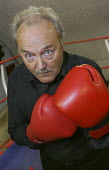 George Galloway MP tests his muscle on a visit to the KO Boxing Club in Bethnal Green. East London. - Jess Hurd - ,2000s,2005,boxer,boxers,boxing,campaign,campaigning,CAMPAIGNS,club,clubs,glove,gloves,Hamlets,POL Politics,SPO sport,Tower,UK