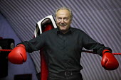 George Galloway MP tests his muscle on a visit to the KO Boxing Club in Bethnal Green. East London. - Jess Hurd - 2000s,2005,boxer,boxers,boxing,campaign,campaigning,CAMPAIGNS,club,clubs,glove,gloves,Hamlets,POL Politics,SPO sport,Tower,UK
