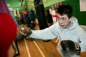 Youth training at the St Georges Boxing Club. Poplar Boys and Girls Club. Tower Hamlets, East London. - Jess Hurd - 2000s,2005,adolescence,adolescent,adolescents,amateur,bag,bags,box,boxer,boxers,boxes,boxing,boy,boys,child,CHILDHOOD,children,cities,city,club,clubs,east end,EXERCISE,exercises,exercising,fight,fight