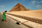 Street cleaner sweeps at the base of the Pyramid of Khufu, Cheops c.2585-2560 B.C.E., the largest of the three principal pyramids on the Giza Plateau. Cairo, Egypt. - Jess Hurd - ,2000s,2005,african,Africans,arab,arabic,arabs,arid,BME black minority ethnic,cleaner,cleaners,CLEANING,cleansing,dry,EBF Economy,egypt,egyptian,highway,holiday,holiday maker,holiday makers,holidaymak