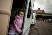 Young girl looks out of her caravan onto a bleak traveller site with no facilities. The site is overlooked by Bow Quarter - a luxury gated development in Tower Hamlets, East London. - Jess Hurd - 06-04-2005