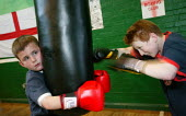 Young people train at the St Georges Boxing Club. Poplar Boys and Girls Club. Tower Hamlets, East London. - Jess Hurd - 2000s,2005,adolescence,adolescent,adolescents,amateur,box,boxer,boxers,boxes,boxing,boy,boys,child,CHILDHOOD,children,cities,city,club,clubs,east end,exercise,exercises,exercising,fight,fighter,fighte