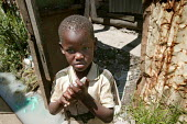 Child stands outside his house with filthy stagnant water in Huruma slum. ActionAid Get on Board campaign. The Joburg to G8 bus is collecting messages to take to the world leaders at the G8 Summit in... - Jess Hurd - 04-05-2005