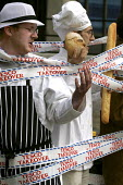 ActionAid Corporate Muscle intimidates a local butcher, baker and grocer in a theatrical protest against supermarket Tesco and their monopoly of the industry. Organised by Friends of the Earth and Act... - Jess Hurd - 24-06-2005
