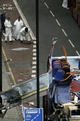 Police forensic officers sift the ground for evidence surrounding the destroyed bus blown up a bomb in Tavistock Square, London. - Jess Hurd - 08-07-2005
