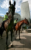 Mounted police at Canary Wharf. Horses are deployed under conditions of heightened security to deter bombers from entering the tube station. Docklands, East London. - Jess Hurd - 2000s,2005,adult,adults,American,americans,animal,animals,bank,banking,banks,beat,Canary Wharf,capitalism,capitalist,Citi,Citibank,cities,Citigroup,city,CLJ law and justice,commute,commuter,commuters,