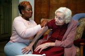 District nurse gives a flu jab to an elderly patient on their rounds in Poplar, Tower Hamlets, East London. - Jess Hurd - 2000s,2005,adult,adults,against,age,ageing population,arm,arms,BAME,BAMEs,being,bme,BME black minority ethnic,bmes,care,carer,carers,cities,city,diversity,dose,doses,elderly,ethnicity,FEMALE,HEA healt