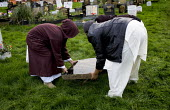 Muslim youth repair the damage to graves in Handsworth cemetery in a suspected racist attack. The day of the Muslim festival Eid, Birmingham. - Jess Hurd - ,2000s,2005,anti social behavior,anti social behaviour,anti socialanti social behavior,antisocial,antisocial behaviour,antisocialvandalise,antisocialvandalize,attack,attacked,attacking,bigotry,broken,