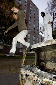 The youth of Aulnay Sous Bois celebrate their defiance on the burnt out vehicles that litter their estate after nights of rioting. Paris, France. - Jess Hurd - 11-11-2005
