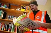 World Book Day at Mount Pleasant Sorting Office. Royal mail worker with a new book borrowing shelf at Mount Pleasant Sorting Office in North London. - Jess Hurd - 02-03-2006