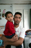 Shamsul Alam Harun and his son Thasin (2). The family of 5 are living in one room due to the appalling damp conditions in their flat which has resulted in sever eczema for their eldest child. Bow, Tow... - Jess Hurd - 2000s,2006,Asian,Bengali,BME Black minority Ethnic,child,CHILDHOOD,children,cities,city,class,conditions,CROWDED,DAD,DADDIES,DADDY,DADS,damp,disrepair,east end,EQUALITY,excluded,exclusion,families,fam