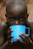Child drinks some water in Kibera - the largest slum in Africa. Nairobi, Kenya. - Jess Hurd - 25-06-2005