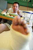Patient with a fractured shin bone, both Tibia and Fibular eating food. Charing Cross Hospital. London. - Jess Hurd - 13-03-2007
