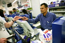Staff working at the checkout. Tesco Metro, Bishopsgate, London. - Jess Hurd - 17-04-2007