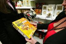Customers compare brand for fat content. Tesco Metro, Bishopsgate, London. - Jess Hurd - 17-04-2007