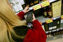 Tesco staff check prices on the shelves. Tesco Metro, Bishopsgate, London. - Jess Hurd - 17-04-2007