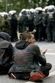 Anarchists sit in front of a police line on a demonstration outside the Rostock Refugee Camp. Flight and Migration Day of Action. Protests at the G8 summit in Heiligendamm, Rostock, Germany. - Jess Hurd - 04-06-2007