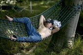 Protester uses a section of G8 fence as a hammock. Block G8 protests at the G8 summit in Heiligendamm, Rostock, Germany. - Jess Hurd - 07-06-2007