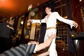 Elvis Presley tribute act in an East End pub, London. - Jess Hurd - 2000s,2007,ACE arts culture & entertainment,adoration,and,audience,AUDIENCES,cities,city,dance,dancer,dancers,dancing,entertainer,entertaining,fan,fans,impersonate,impersonating,impersonator,impersona