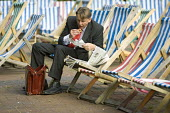 Businessman sits eats his lunch on a deckchair in a London park. - Jess Hurd - 04-09-2007
