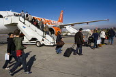 Passengers board an Easyjet aeroplane at Marrakech Airport, Morocco. - Jess Hurd - 2000s,2008,aeroplanes,Africa,african,africans,air transport,aircraft,airline,Airport,AIRPORTS,arab,arabs,aviation,bag,baggage,bags,boarding,budget,cheap,cost,EBF Economy,flight,flights,fly,flying,grou