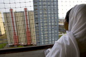 Asylum seeker looks out the window of her Red Road Flats, Glasgow, Scotland. - Jess Hurd - 29-12-2007