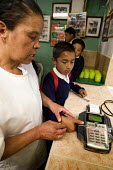 Children are electronically fingerprinted before they can have lunch at a community subsidised kitchen. Cuidad Bolivar, South Bogota, Colombia. - Jess Hurd - 07-02-2008