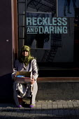 Elderly woman sells tissues outside a Levis Jeans store with the slogan Reckless and Daring. Istanbul, Turkey. - Jess Hurd - ,2000s,2008,age,ageing population,Asia,asian,asians,cities,city,dress,EBF economy,elderly,EQUALITY,Europe,excluded,exclusion,female,hajib,HARDSHIP,headscarf,hijab,impoverished,impoverishment,INEQUALIT