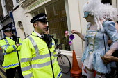 Space Hijacker tries to crown a policeman as May King. Celebrating a traditional May Day, Mayfair, London. - Jess Hurd - 2000s,2008,ace art culture,activism,activist,activists,adult,adults,anarchist,ANARCHISTS,anarchy,CAMPAIGN,campaigner,campaigners,CAMPAIGNING,CAMPAIGNS,CELEBRATE,Celebrating,CLJ,costume,costumes,cross