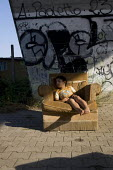 Child sleeps in an armchair at a Roma Gypsy camp underneath a motorway flyover in South West Rome, Italy. - Jess Hurd - ,2000s,2008,asleep,BAME,BAMEs,BME,bmes,camp,camps,child,CHILDHOOD,children,communities,community,diversity,EQUALITY,ethnic,ethnicity,eu,Europe,european,europeans,eurozone,excluded,exclusion,EXHAUSTION