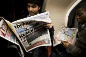 Commuters on the Tube read The london Paper with the headline: Black Friday. After Panic selling on the stock market City of London. - Jess Hurd - ,2000s,2008,adult,adults,anxiety,anxious,ANXIOUSNESS,APPREHENSIVE,bad,BAME,BAMEs,bank,bank worker,bank workers,banking,banks,bankworker,bankworkers,Black,BME,bmes,buy,buyer,buyers,buying,carriage,carr