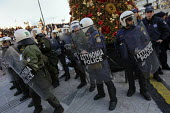 Riot police protect a Christmas tree from demonstrators throwing rubbish and pork bones. Demonstration called after the fatal shooting by the police on Dec. 6 of a 15-year-old, Alexandros Grigorolopou... - Jess Hurd - 20-12-2008