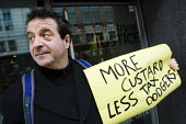 Mark Thomas, demonsrtates against the off-shore ownership of the Home Office and calls for more custard less tax dodgers. London. - Jess Hurd - 2000s,2009,activist,activists,against,avoidance,BANK,banks,CAMPAIGN,campaigner,campaigners,CAMPAIGNING,CAMPAIGNS,comedian,COMEDIANS,comedy,crisis,DEMONSTRATING,demonstration,DEMONSTRATIONS,depression,