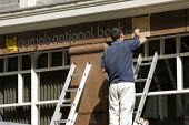 Worker paints the lettering for the sign. Punjab National Bank, City of London. London. - Jess Hurd - 18-04-2009