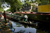 A man trying to pump water out of a sinking barge on the Regents Canal. Hackney, East London. - Jess Hurd - 2000s,2009,barge,barges,bilge,boat,boats,canal,canals,cities,city,enthusiast,enthusiasts,Hackney,hobbies,hobby,hobbyist,holiday,holidays,inland,LFL Leisure,narrow boat,pump,pumping,pumps,sink,sinking,